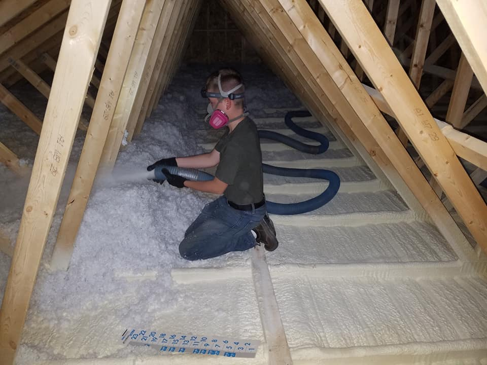 worker blowing insulation on top of spray foam insulation in an attic