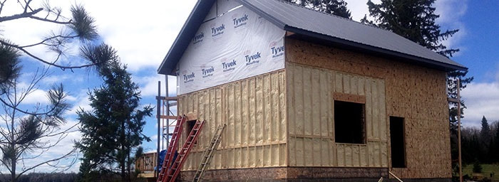 applying air barrier and insulation to exterior of home
